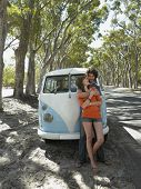 picture of campervan  - Young couple embracing leaning against front of camper van parked by road - JPG