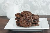 A Stack Of Chocolate, Chocolate Chip Cookies On A White Plate.