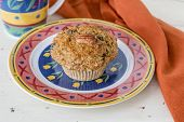 A homemade pecan carrot muffin on a decorative plate.
