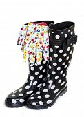 A colorful gardening outfit with polka dot rubber boots and floral patterned gardening gloves. Focus