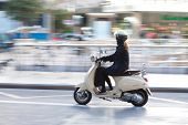 VALENCIA, SPAIN - JANUARY 27, 2014: A woman on a Vespa scooter traveling in the town center of Valencia with motion blur. Vespa is an Italian brand of scooter manufactured by Piaggio.