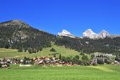 Gorgeous weather in the resort town of Leysin in the Swiss Alps. Picturesque gentle alpine meadows and rural houses chalets
