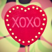 picture of a heart-shaped lollipop with the text XOXO, hugs and kisses, written in it, with a retro