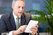 Mature businessman using his tablet in his office
