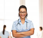 healthcare and medicine concept - smiling female african american doctor or nurse in eyeglasses with stethoscope
