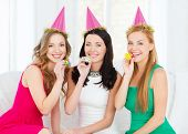 celebration, friends, bachelorette party, birthday concept - three smiling women wearing pink hats a