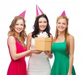 celebration, friends, bachelorette party, birthday concept - three smiling women wearing pink hats w
