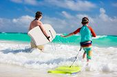 Mother and son running towards ocean with boogie boards