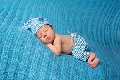 stock photo of pajamas  - Newborn baby sleeping on a blue blanket and wearing vintage inspired blue and white striped pajamas with matching sleeping cap - JPG