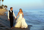 Happy wedding couple walking on the beach