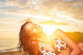 Beautiful young woman in bikini on the beach at sunset