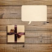 Gift Box And Speech Bubble On Wooden Background
