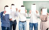 Highschool students holding sheets of blank paper in front of heads