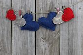 Red, blue calico and wood hearts hanging on clothesline with wood background