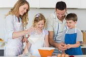 Happy family making cookies together in kitchen