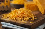 stock photo of shredded cheese  - Organic Shredded Sharp Cheddar Cheese on a Cutting Board