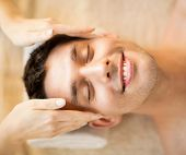 healthcare, spa and beauty concept - man is getting massage at in spa salon