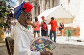 HAVANA,CUBA - JANUARY 20, 2014:Old black lady smoking a huge cuban cigar next to the havana Cathedra