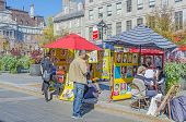 MONTREAL, CANADA, OCTOBER 12, 2013 - tourists watch an artist painting and selling his caricatures i