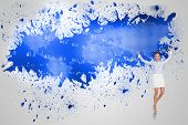 Excited brunette businesswoman jumping and cheering against splash on wall revealing blue world map