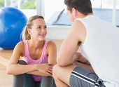Smiling young fit couple chatting in a bright exercise room