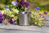 pic of ferrous metal  - metal mug campaign is on the gray wooden table with a bunch of different wildflowers - JPG