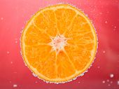 Fresh orange in water with bubbles on red background