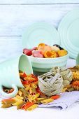 Colorful pasta in color bowls and mugs on wooden background