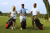 Happy partners standing on golf course, choosing golf club from golfing kit, starting game.