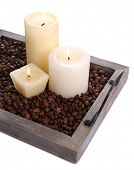 Candles on vintage tray with coffee grains, isolated on white