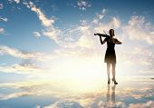 Silhouette of woman playing violin at sunset