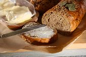 Baked bread and toast with fresh butter, on cutting board, on wooden background