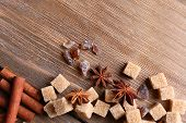 Brown sugar cubes and spices on wooden background