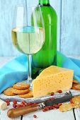 Wine, cheese and crackers on wooden table close-up