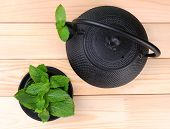 Chinese traditional teapot with mint leaves on wooden background