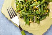 Salad with green beans and corn, on plate, on color wooden background