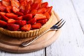 Strawberry tart on color wooden background