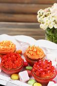Tasty cupcakes on wooden table, close up