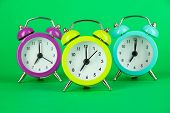 Colorful alarm clock on green background