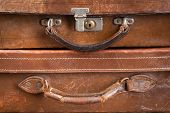 Detail of two very old brown leather locked suitcases