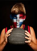 portrait of basketball player with Dominican Republic flag painted on his face