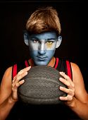 portrait of basketball player with argentinian flag painted on his face