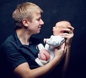 father and his newborn baby daughter over black background