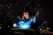 Little Halloween witch making magic with stick