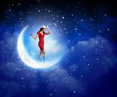 Young woman in red dress walking on moon