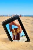 a tablet on the sand of a beach with a picture of a man with a glass of cola drink