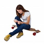 Woman sitting on skateboard and using smart phone.