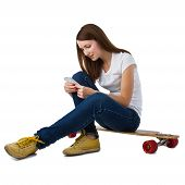 Young woman sitting on skateboard and using smart phone. Isolate