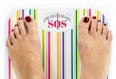 pic of sos  - Feet on bathroom scale with word  - JPG