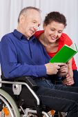 Disabled And A Nurse Reading A Book Together